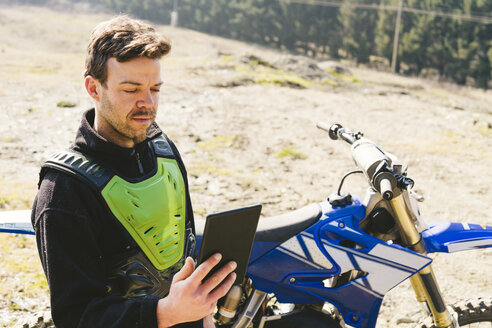 Portrait of motocross driver looking at tablet - FBAF00349