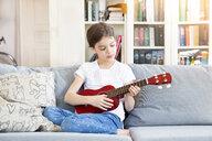Portrait of girl sitting on couch at home playing ukulele - LVF07926