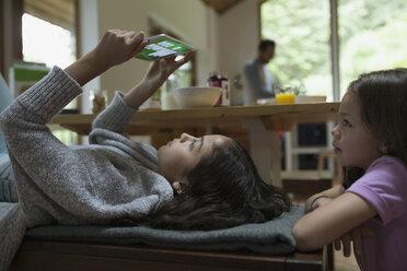 Sisters playing video games on digital tablet at breakfast table - HEROF32169