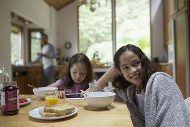 Smiling girl enjoying breakfast at kitchen table - HEROF32172