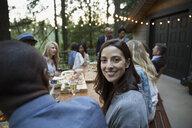 Portrait smiling woman enjoying dinner party on cabin balcony - HEROF32190
