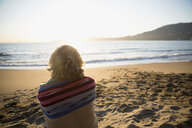 Serene woman wrapped in blanket looking at sunset ocean view - HEROF32211