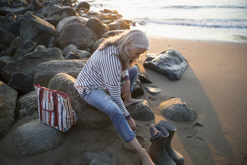 Senior woman taking off rubber boots and putting on sandals on beach - HEROF32217