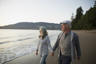 Senior couple holding hands walking on beach looking at ocean - HEROF32223