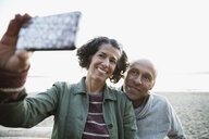 Smiling couple taking selfie with camera phone on beach - HEROF32238