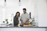 Smiling couple drinking wine and cooking in kitchen - HEROF32247