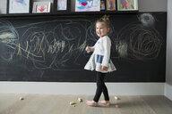Smiling girl drawing on blackboard wall - HEROF32253