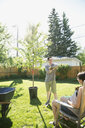 Pregnant couple planting tree in sunny backyard - HEROF32256