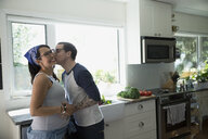 Pregnant couple kissing in kitchen - HEROF32259