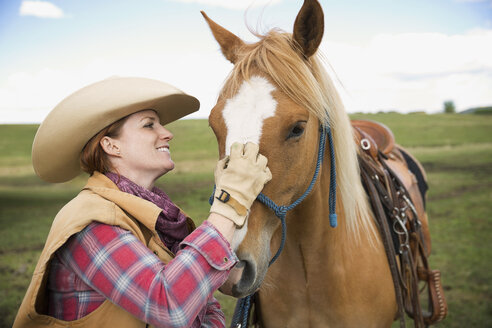 Smiling female cattle rancher petting horse - HEROF32268