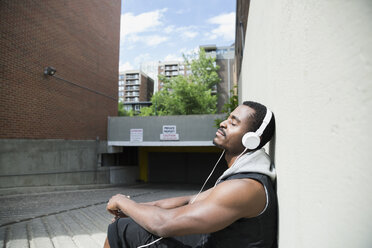 Serene young man listening to music with headphones at sunny parking garage entrance - HEROF32274