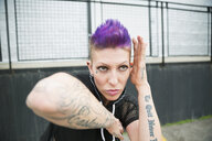 Portrait tough cool young woman with purple mohawk and tattoos - HEROF32280