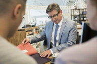 Salesman showing couple fabric swatches in home furnishings store - HEROF32307