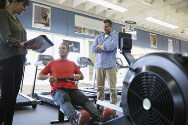 Salesman demonstrating rowing machine for couple in home gym equipment store - HEROF32310