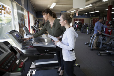 Saleswoman helping woman shopping for treadmill in home gym equipment store - HEROF32313