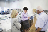 Saleswoman with digital tablet helping senior couple in appliance store - HEROF32334