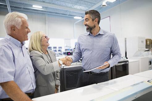Salesman handshaking with senior couple in appliance store - HEROF32337