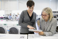 Saleswoman with digital tablet helping senior woman shopping for clothes washer in appliance store - HEROF32340