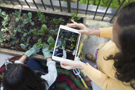 Overhead view girl with digital tablet photographing mother gardening - HEROF32370