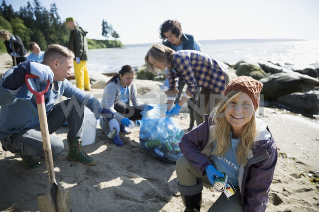 Portrait smiling beach cleanup volunteer picking up litter on sunny beach - HEROF32382 - Hero Images/Westend61