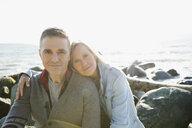 Portrait affectionate couple hugging on sunny beach rocks - HEROF32415
