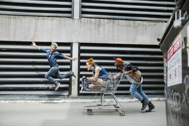 Playful cool young friends pushing shopping cart in urban alley - HEROF32451