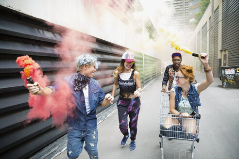 Playful young friends with shopping cart and color powder cannons on urban street - HEROF32457