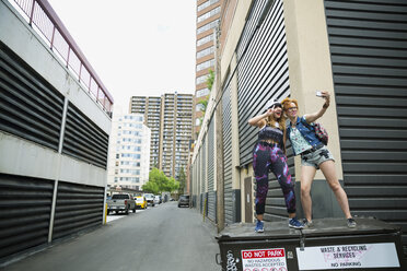 Playful cool young women taking selfie on dumpster in urban alley - HEROF32460