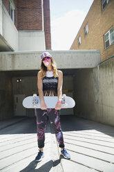 Portrait cool young woman holding skateboard at urban parking garage entrance - HEROF32472