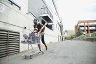 Playful cool young man pushing woman in shopping cart on urban sidewalk - HEROF32475