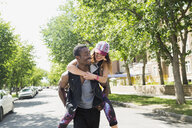 Playful young couple piggybacking on sunny street - HEROF32478