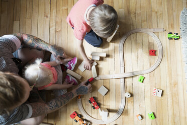 Overhead view of father and children playing with wood blocks and toy train on floor - HEROF32520