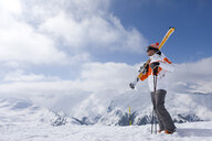 Skier on remote mountain top carrying skis - JUIF00624