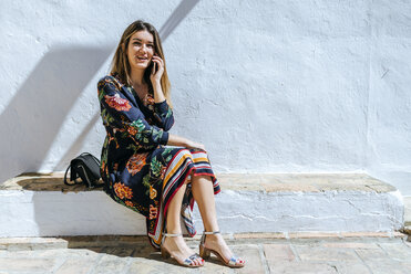 Spain, Cadiz, Vejer de la Frontera, portrait of fashionable woman on the phone sitting on wall - KIJF02446