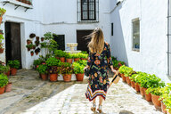 Spain, Cadiz, Vejer de la Frontera, back view of fashionable woman standing at patio - KIJF02452