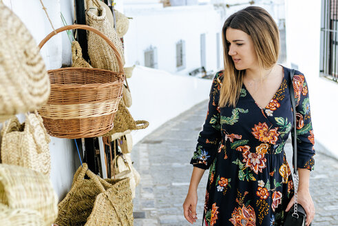 Spain, Cadiz, Vejer de la Frontera, fashionable woman looking at bags and baskets at a shop - KIJF02458