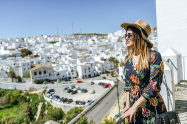 Spain, Cadiz, Vejer de la Frontera, fashionable woman standing on roof terrace looking at view - KIJF02461