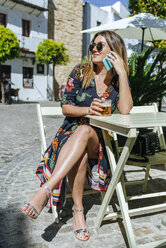 Spain, Cadiz, Vejer de la Frontera, young woman on the phone sitting at street cafe with glass of beer - KIJF02470