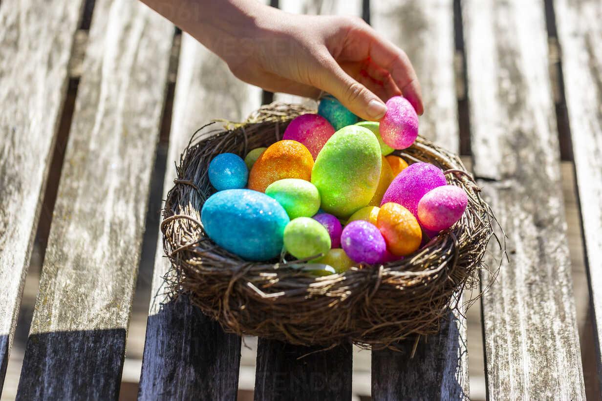 Girl taking Easter egg from Easter nest - SARF04197 - Sandra Roesch/Westend61