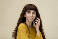 Portrait of young woman with freckles on the phone - FLLF00083