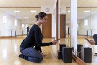 Ballet dancer using cell phone in ballet studio - FMOF00458