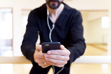 Close-up of ballet dancer using cell phone in ballet studio - FMOF00461