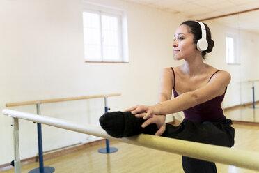 Ballet dancer with headphones stretching in ballet studio - FMOF00467
