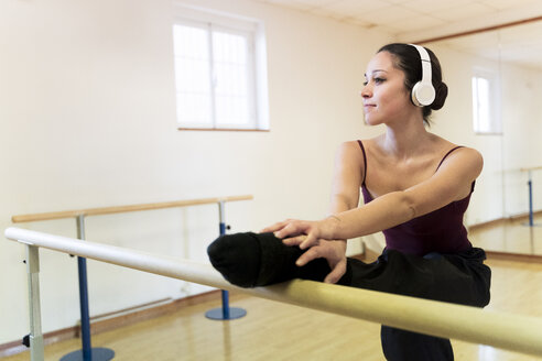 Ballet dancer with headphones stretching in ballet studio - FMOF00467