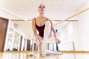 Ballet dancer putting on shoes - FMOF00473
