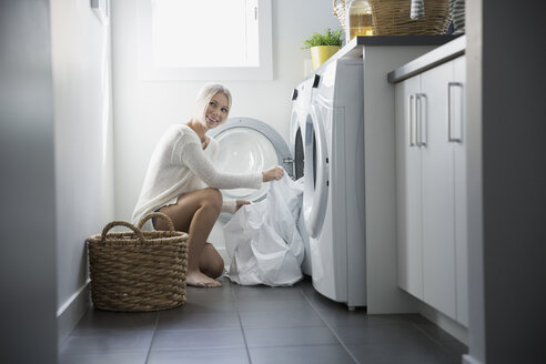 Woman removing sheets from dryer in laundry room - HEROF32560