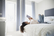 Young woman using digital tablet on bed - HEROF32581