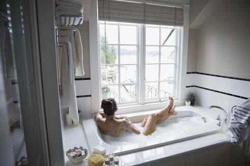 Woman enjoying bubble bath with lake view - HEROF32605