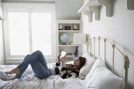 Teenage girl laying using digital tablet on bed - HEROF32614