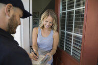 Woman signing for delivery at front door - HEROF32626